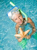 Snorkel girl with starfish on summer vacation - space for text