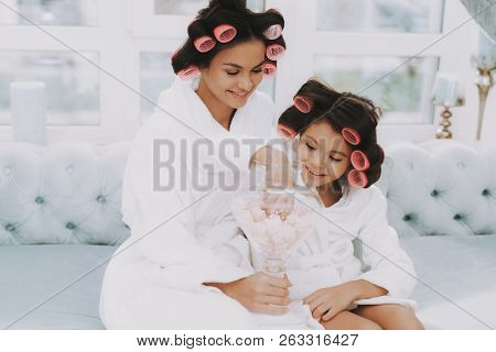 poster of Little Lady With Curlers. Mother And Daughter In Spa. Consept Beauty Salon. Girl And Mom Eating Swee