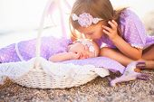 Little Sisters Are On Sea Beach. Two Girls Are In Lilac And Lavender Dresses. Baby Is Sleeping In Wi poster