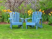 foto of lawn chair  - Blue wooden lawn chairs in the spring garden - JPG