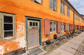 Yellow Facade Of Old Building In Traditional Style In Copenhagen, Denmark. Bicycle Parked At Door Of poster