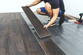 Laminate Flooring - Worker Installing New Floor poster