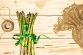 Composition Of Lot Of Whole Fresh Green Asparagus Spear Tied By Green Ribbon Flatlay On Natural Wood poster