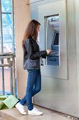 image of automatic teller machine  - The girl draws out money in a cash ATM - JPG