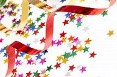stock photo of reveillon  - red and golden ribbons and small confetti colorful stars - JPG