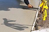 A Concrete Laborer Trowels Wet mud Concrete On A Sidewalk Repair Project. poster