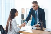 Professional Lawyer And Young Female Client Shaking Hands In Office poster