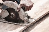 Hand Of A Carpenter Using A Circular Saw To Cut A Wooden Plank. Tool Used To Saw Wood. Carpentry Too poster
