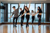 Group Of Attractive Asian People Performing Graceful Dance Movement While Dancing In Stylish Studio  poster