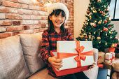 Girl Holding Christmas Box Sitting Next To Tree poster