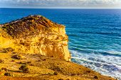 The Great Ocean Road. Steep and rocky ocean shore of Australia. Powerful ocean surf at sunset. The c poster