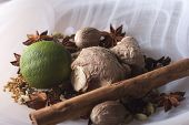 stock photo of vedic  - closeup of Ayurvedic ingredients a lime with whole spices in smoky white glass bowl - JPG
