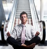 stock photo of stressless  - Businessman meditating in lotus position in front of an escalator indoor - JPG