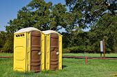 stock photo of porta-potties  - Two yellow portable toilets at a park - JPG