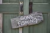 pic of fisherman  - Gone fishing sign on old green door - JPG