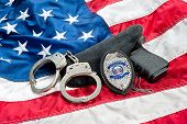 Police badge, gun and handcuffs on an American flag symbolizing law enforcement in the United States
