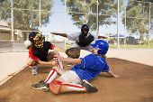 Softball player sliding into base with baseman and umpire