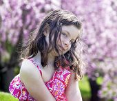 stock photo of coy  - Coy little girl sitting in a garden - JPG