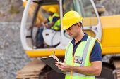 stock photo of bulldozer  - construction manager writing report at construction site - JPG