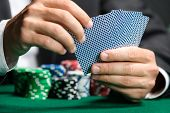 picture of poker hand  - Gambler playing poker cards with poker chips on the table - JPG