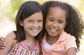 Постер, плакат: Две молодые друзья девушки сидя на открытом воздухе улыбается