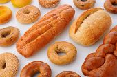 A large group of breads and bagels viewed for overhead on white with reflection. Items include: sesa