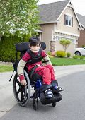 stock photo of biracial  - Disabled biracial six year old boy sitting in wheelchair on sidewalk - JPG