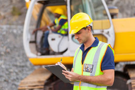 image of ppe  - construction manager writing report at construction site - JPG