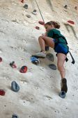 stock photo of climbing wall  - Teen taking a large tep up on an artificial wall - JPG
