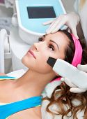 stock photo of ultrasonic  - Woman getting laser face treatment in medical spa center - JPG