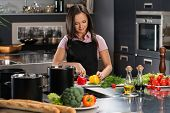 stock photo of apron  - Cheerful young woman in apron on modern kitchen cutting vegetables - JPG