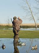 picture of duck-hunting  - A hunter calling ducks on his duck call - JPG