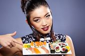 stock photo of sushi  - Sushi woman holding sushi with chopsticks looking at the camera smiling - JPG