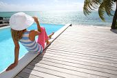 pic of infinity pool  - Rear view of fashion girl sitting by infinity pool - JPG