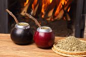 stock photo of calabash  - Hot mate in calabashes on the background the fireplace - JPG