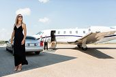stock photo of limousine  - Full length of rich woman in elegant dress standing against limousine and private - JPG
