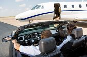 stock photo of cabin crew  - Rear view of pilot and stewardess in convertible parked against private jet at terminal - JPG