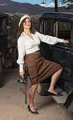 stock photo of tommy-gun  - Beautiful 1920s gangster woman with gun next to car - JPG