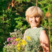 picture of average looking  - Woman with bouquet of wild flowers on walk in summer wood - JPG