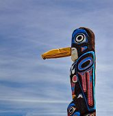 pic of totem pole  - Old totem pole on the background of cloudy sky - JPG