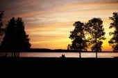 stock photo of elderly couple  - Elderly couple silhouetted sitting on a bench by lake at sunset - JPG