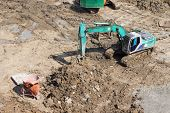 pic of backhoe  - Truck Backhoe Soil Excavation And Soil Movement In Construction Site - JPG