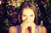 pic of allergies  - Young woman with allergy during sunny day is wiping her nose - JPG
