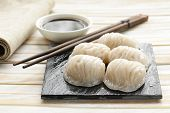 stock photo of soy sauce  - Asian steamed meat dumplings dim sum with soy sauce - JPG