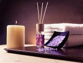 stock photo of violet  - Spa massage border background with towel stacked perfume diffuser and sea salt violet gradient background - JPG