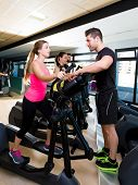 picture of elliptical  - Aerobics elliptical walker trainer personal trainer man at fitness gym workout - JPG