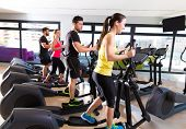 stock photo of treadmill  - Aerobics elliptical walker trainer group at fitness gym workout - JPG