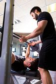 picture of personal assistant  - Bench press weightlifting man with personal trainer in fitness gym - JPG