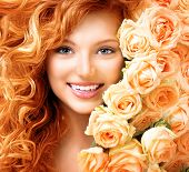image of perm  - Beauty model girl with long curly red hair and beautiful red roses hairstyle - JPG