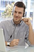 stock photo of dispatch  - Portrait of happy male dispatcher sitting at desk - JPG